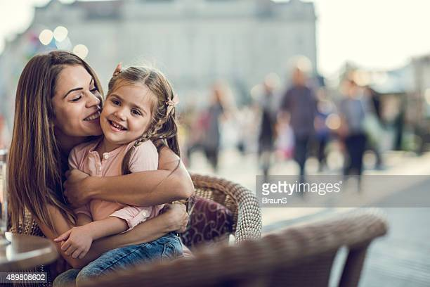 Loving mother embracing her cute daughter on a chair outdoors.