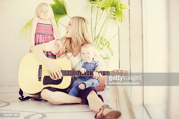 amorevole madre figlio piccolo bambina all'interno - pizzicare le corde di uno strumento foto e immagini stock
