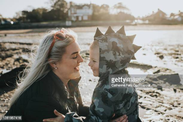loving mother looks adoringly at her son on a cold sunny beach - one parent stock pictures, royalty-free photos & images