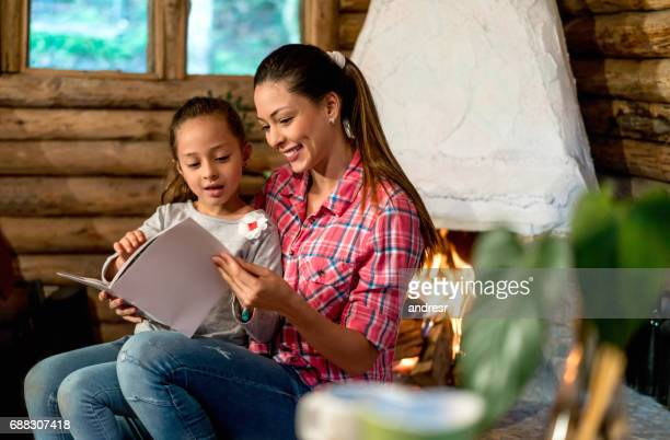 Loving mother reading a book to her daughter at home