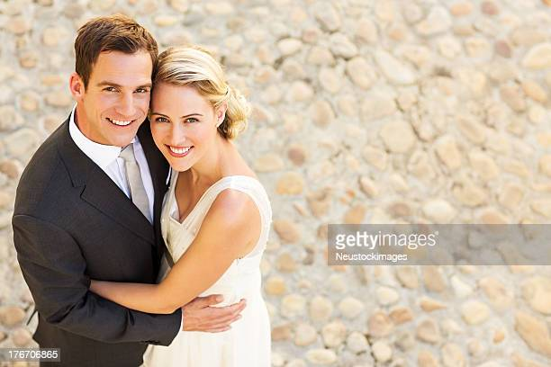 Loving Newlywed Couple Standing Together On Cobblestone