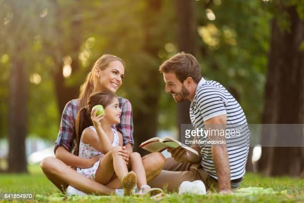 Liebevolle Eltern und Tochter ein Buch im park