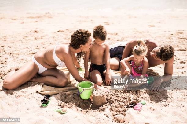 Loving parents enjoying with their small kids on the beach.