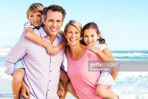 Loving Parents Piggybacking Children On Beach