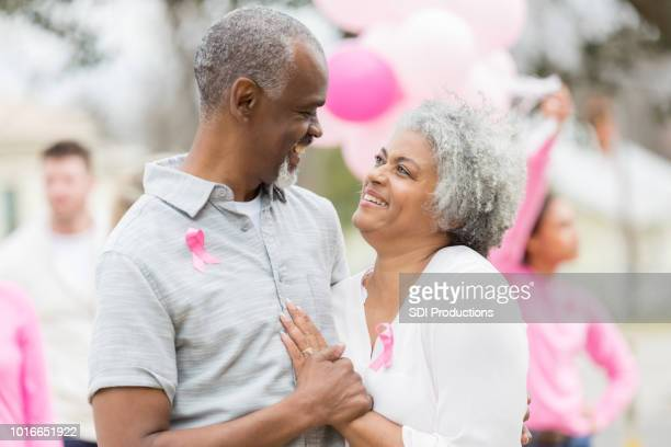 loving senior couple attend cancer awareness furndraiser - survival stock pictures, royalty-free photos & images