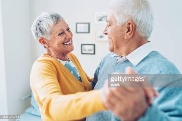 Loving senior couple dancing at home
