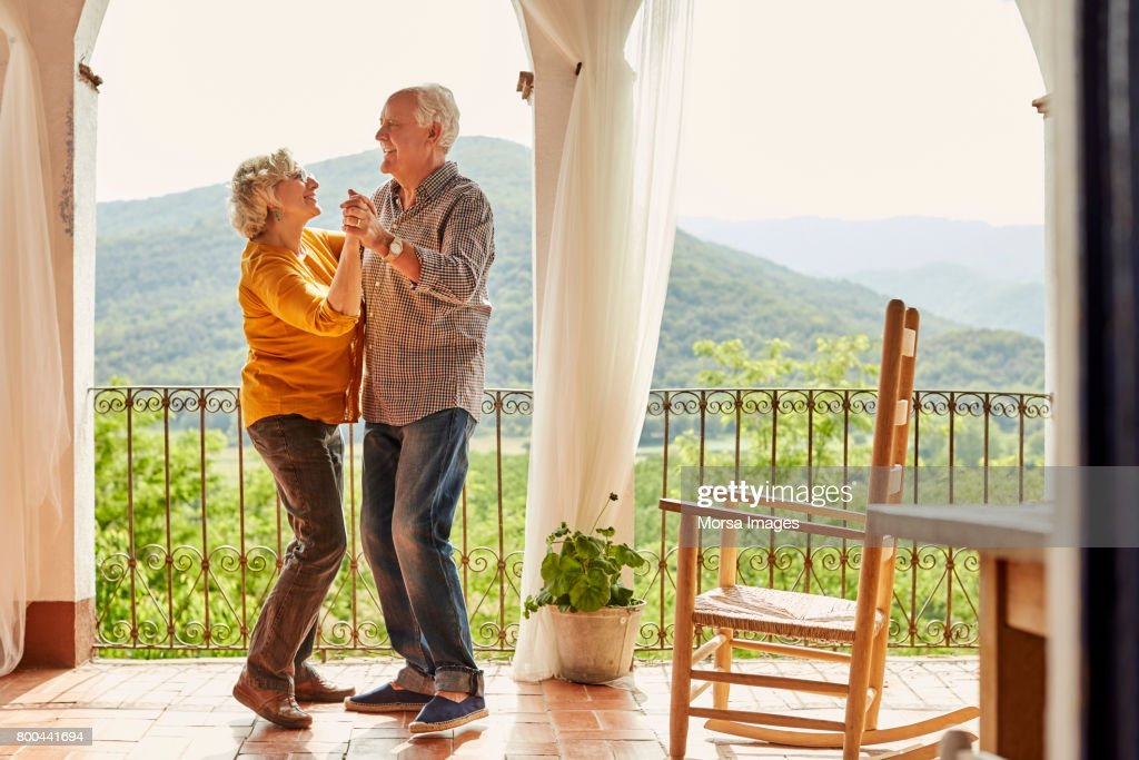 Loving senior couple dancing in balcony at home : Foto de stock