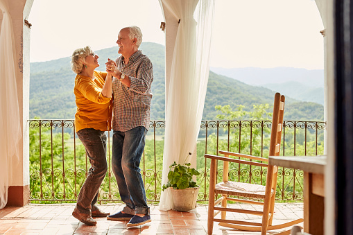 Loving senior couple dancing in balcony at home - gettyimageskorea