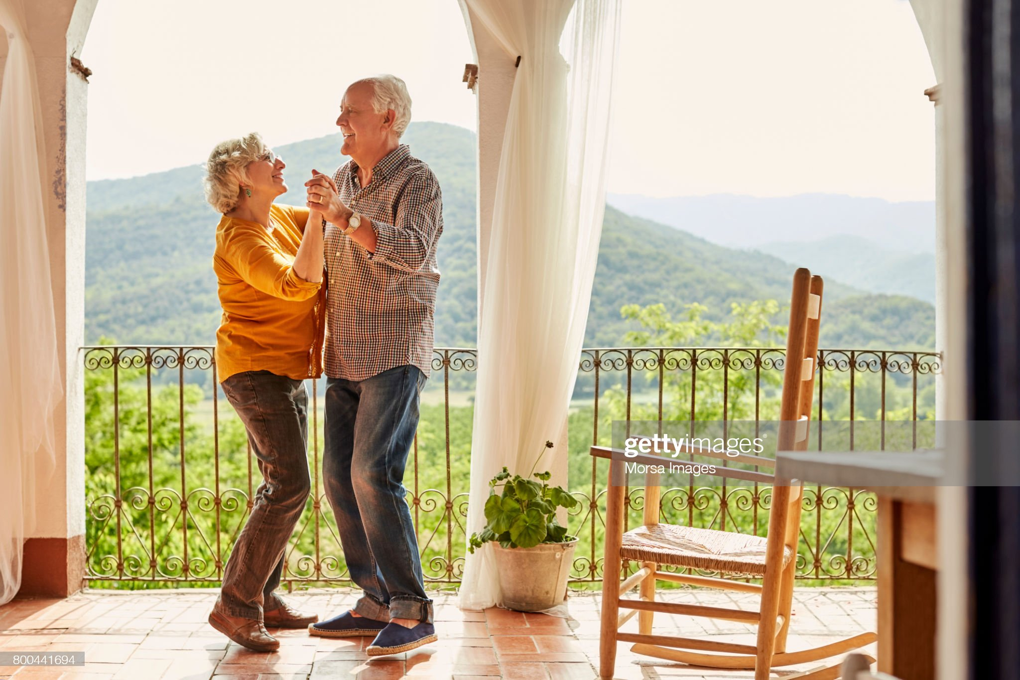 Loving senior couple dancing in balcony at home : Stock Photo