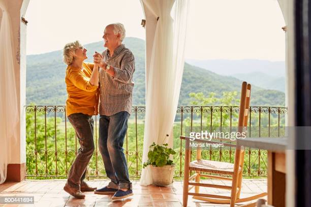 loving senior couple dancing in balcony at home - dancing foto e immagini stock
