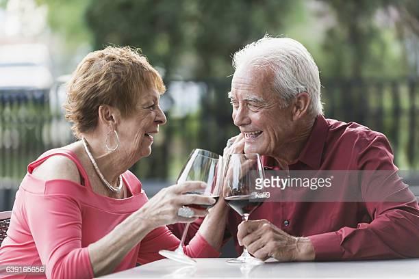 Loving senior couple drinking red wine, talking