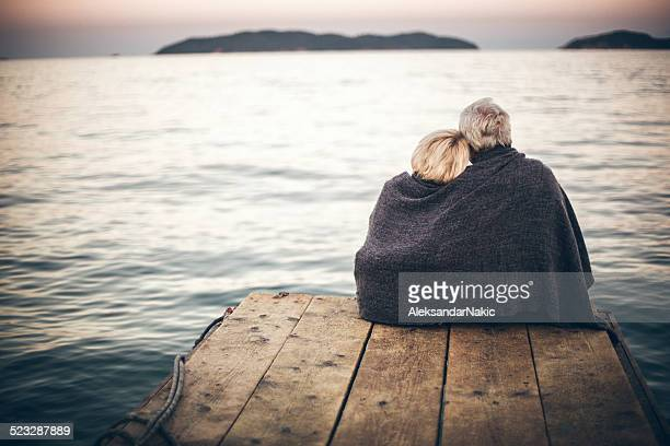 loving senior couple enjoying the view - pier stock pictures, royalty-free photos & images