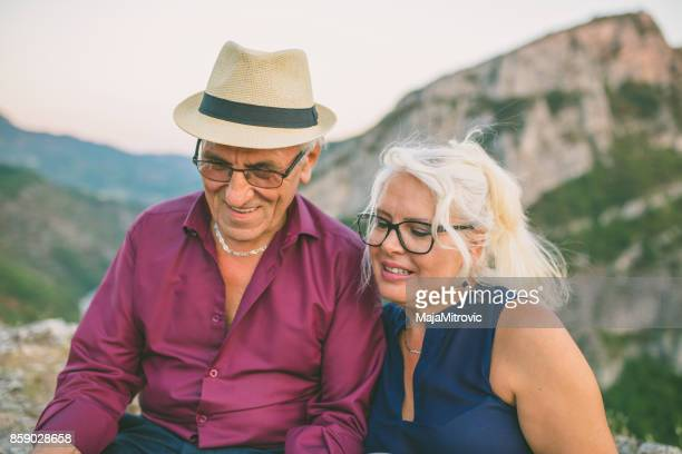 Loving senior couple hiking, sitting on the top of rock, exploring. Active Mature man and woman hugging and Happily smiling.