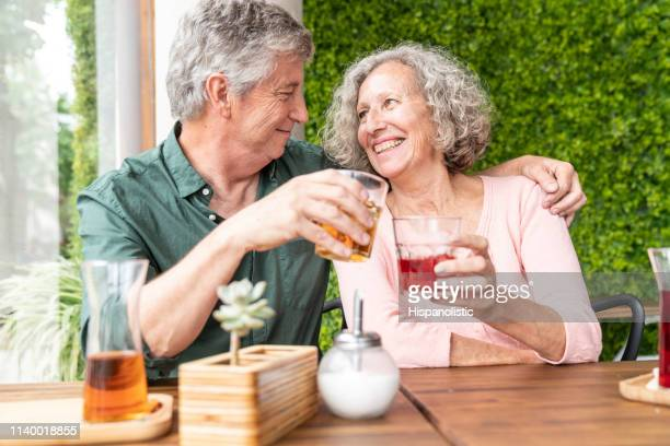 loving senior couple on a date, man hugging woman while toasting with iced tea looking at each other smiling - hispanolistic stock photos and pictures