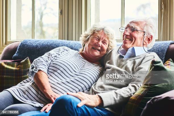 loving senior couple relaxing at home - senior couple stock photos and pictures