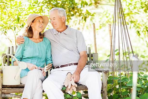 Liebevoll altes Paar mit Gartengerät im Garten