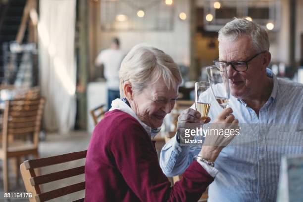 Loving senior man and woman enjoying champagne in restaurant