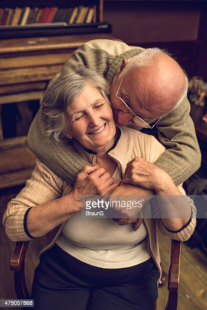Amoroso idoso a beijar e Abraçar sua esposa em casa.