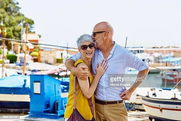 Loving senior man kissing woman against harbor