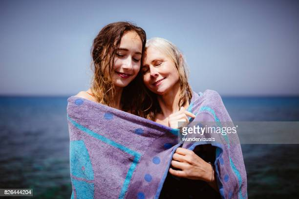 loving senior mother and adult daughter covered in beach towel - mother daughter towel stock photos and pictures