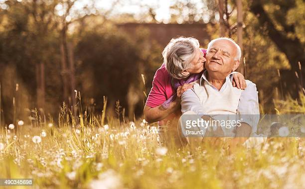 Loving senior woman kissing her husband in grass.