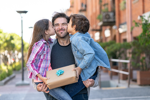 Loving son and daughter kissing daddy on the cheek while he carries them both with a present for father's day 1137603136