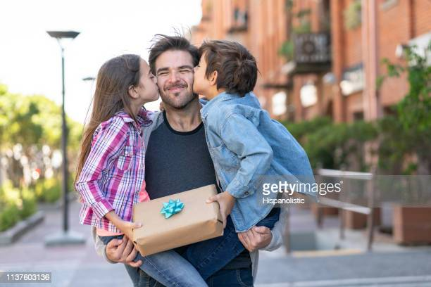 loving son and daughter kissing daddy on the cheek while he carries them both with a present for father's day - gift stock pictures, royalty-free photos & images