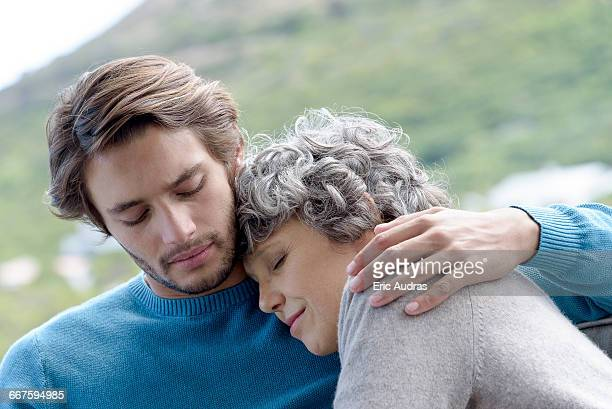 loving son hugging his mother outdoors - young men stock pictures, royalty-free photos & images