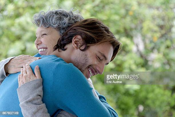 loving son hugging his mother - mother and son stock photos and pictures