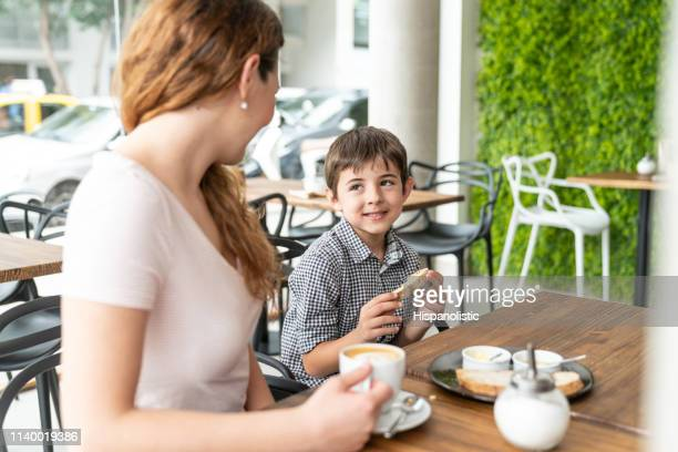 loving son looking at mother while eating a toast with butter - hispanolistic stock photos and pictures