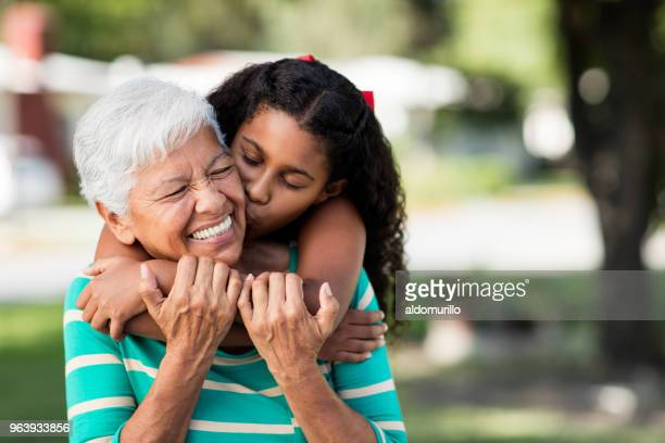 loving teen girl embracing and kissing grandmother - grandmother stock pictures, royalty-free photos & images