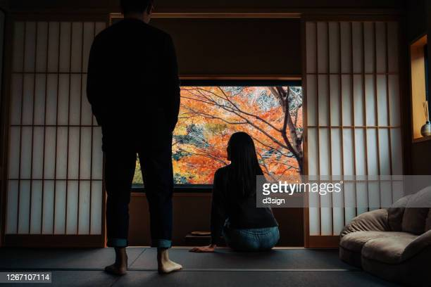 a loving young asian couple relaxing in a traditional japanese style apartment, chatting and enjoying the beautiful nature autumn scenics during the day - japan stock pictures, royalty-free photos & images