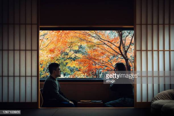 a loving young asian couple sitting by the window in a traditional japanese style apartment, chatting and enjoying the beautiful nature autumn scenics during the day - travel ストックフォトと画像