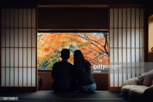 a loving young asian couple sitting side by side by the window in a traditional japanese style apartment, chatting and enjoying the beautiful nature autumn scenics during the day - japan stock pictures, royalty-free photos & images