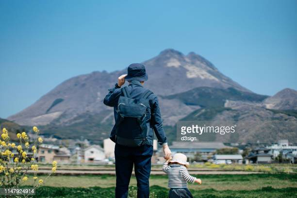 loving young asian father and daughter on a trip in the nature walking outdoors on rape field against blue sunny sky - 郊外の風景 ストックフォトと画像