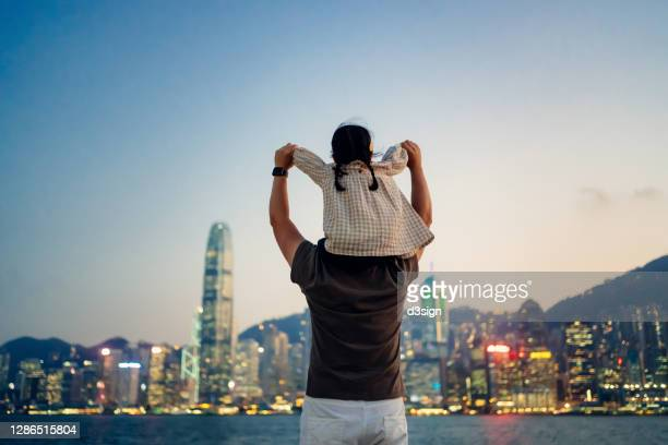 loving young asian father carrying little daughter on shoulders, looking over illuminated urban city skyline against the promenade of victoria harbour at sunset. enjoying father and daughter bonding time together - love stock pictures, royalty-free photos & images