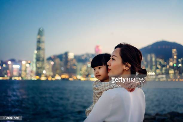 loving young asian mother carrying adorable little daughter in her arms, looking away while standing against the promenade of victoria harbour and illuminated urban city skyline. enjoying intimate mother and daughter bonding time together - hong kong stock pictures, royalty-free photos & images