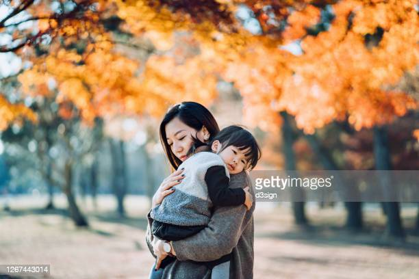 a loving young asian mother embracing adorable little daughter in arms, spending time together and enjoying the beautiful autumn scenics in nature park on a beautiful sunny day - 女性 ストックフォトと画像