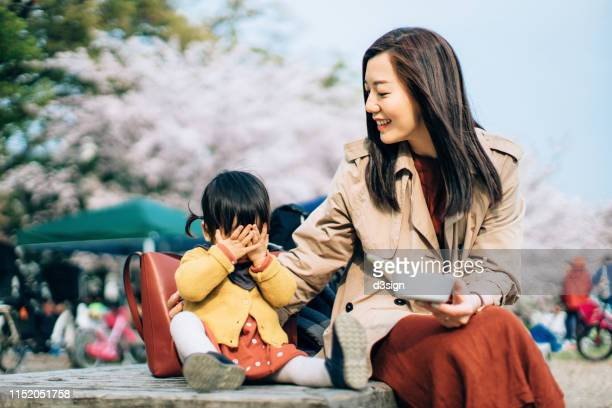 loving young asian mother playing and having fun with cute little daughter in the park against beautiful cherry blossoms on a spring day and are enjoying intimate family time together - 風致地区 ストックフォトと画像