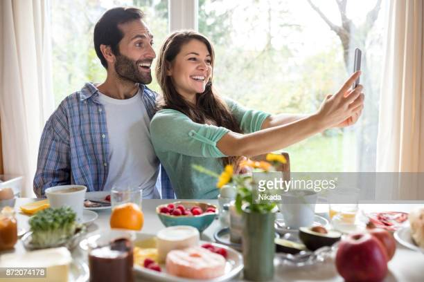 Loving young couple having breakfast and taking a selfie