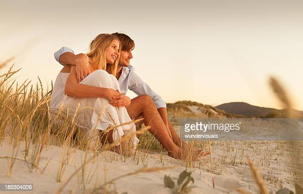 Loving Young Couple Sitting Together On the Beach