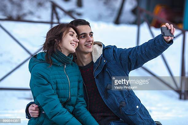 Loving young couple taking selfie through smart phone during winter