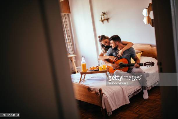 loving young couple with guitar having breakfast in bed - breakfast in bed stock pictures, royalty-free photos & images