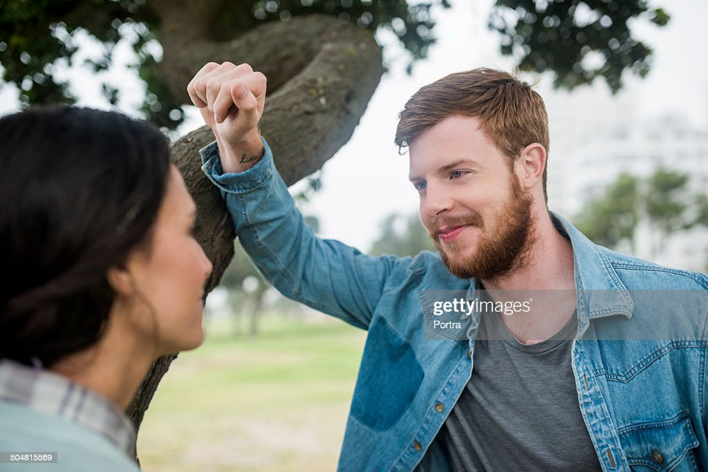 Loving young man looking at woman in park : Stock Photo