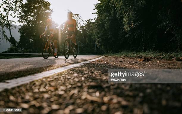 angolo basso 2 asiatico cinese donna ciclista su strada fianco a fianco in bicicletta nella zona rurale al mattino - ciclismo su strada foto e immagini stock