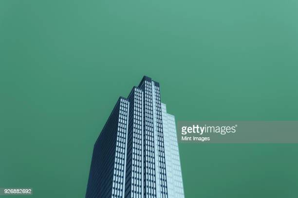 Low angle abstract of modern office building extending towards sky.