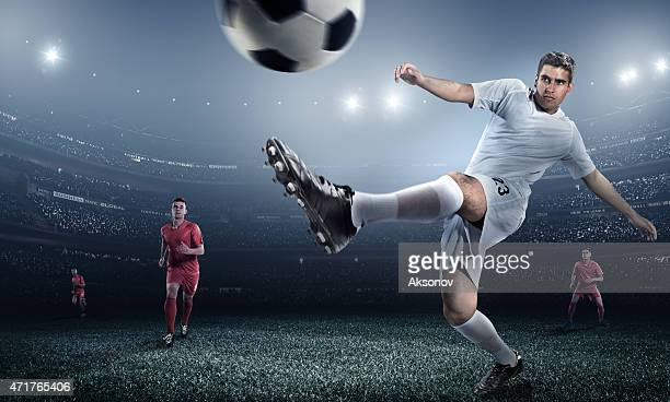 Low angle action shot of a kicked soccer ball and players