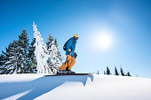 Low angle and full length shot of a skier on top of the mountain enjoying beautiful sunny winter day copyspace active people living leisure hobby extreme slope snow seasonal sport