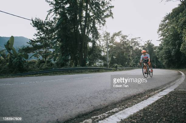 low angle asian chinese woman road bike cyclist sprinting cycling in rural area in the morning - forward athlete stock pictures, royalty-free photos & images