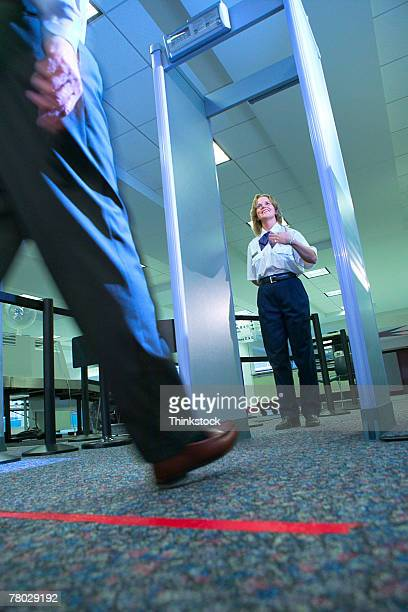 low angle close-up of a business traveler's leg as he prepares to walk through the metal detector at the airport security checkpoint - metal detector security stock pictures, royalty-free photos & images